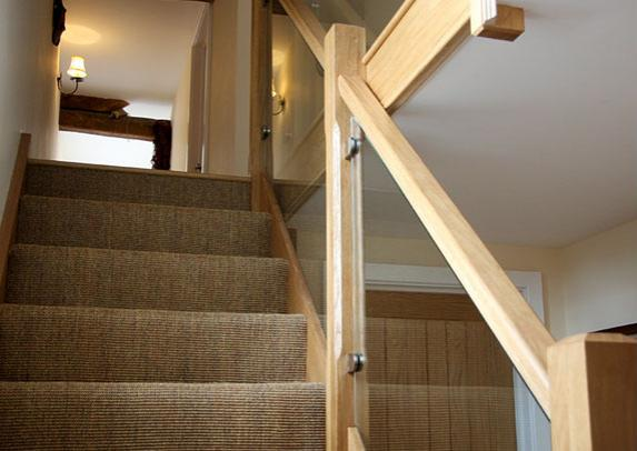 A picture a customer sent in that includes oak rails, metal glass balustrade brackets and custom glass panels to fit.