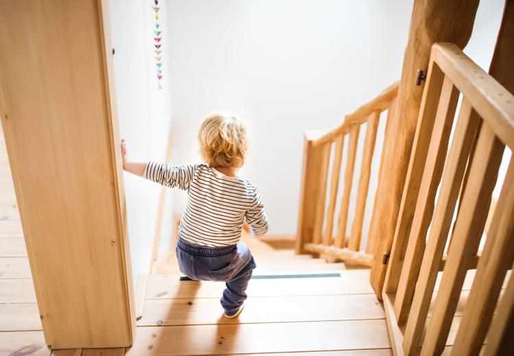 A small child walking down a staircase.