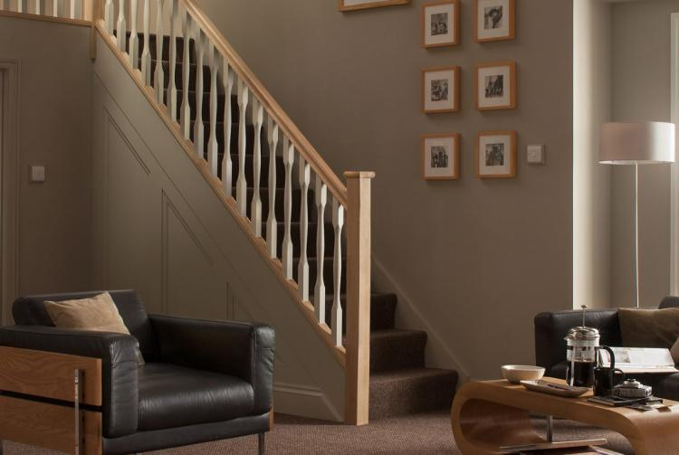 A lifestyle picture of Slender Quays Stair Balustrade that includes White Primed Stair Spindles.