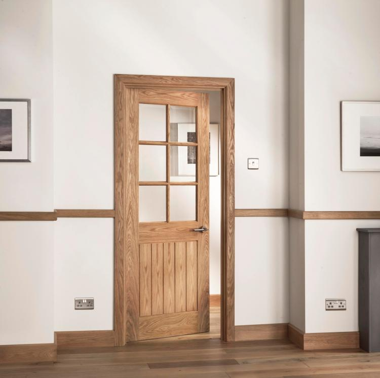 A picture of a glazed interior oak door in a home setting with modern door furniture.