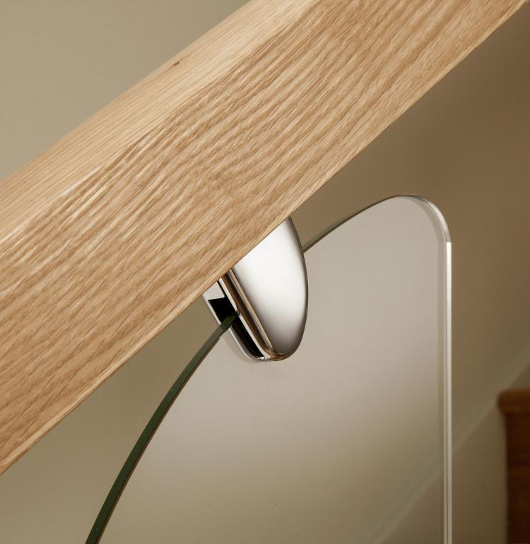 A picture of a stainless steel glass clamp, clear glass panel and solid oak handrail.