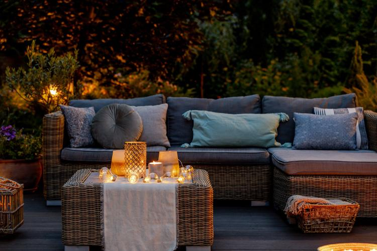 An outdoor decking area in the evening with a luxury rattan corner sofa, table and lit candles.