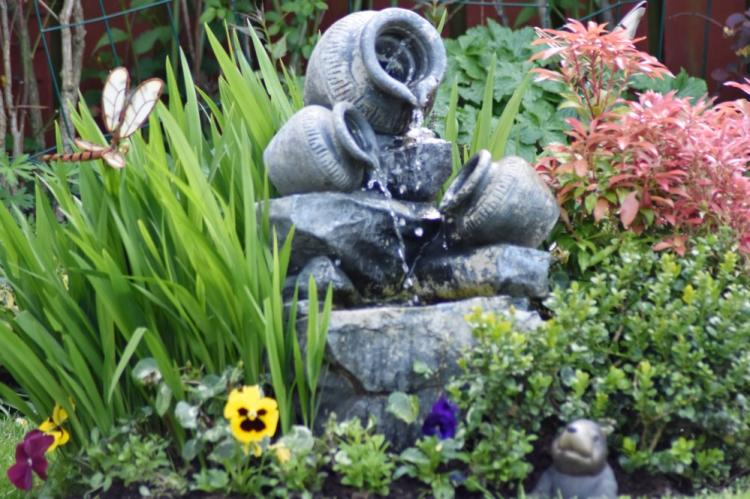 A water fountain amongst flowers and other garden ornaments. A water fountain is a top garden trend in 2021.
