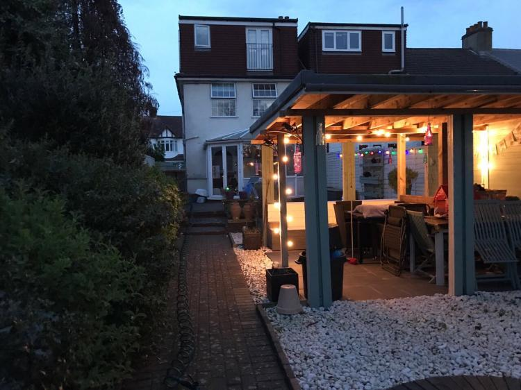A picture of a back garden in the evening that includes a wooden pergola and outdoor garden lighting.