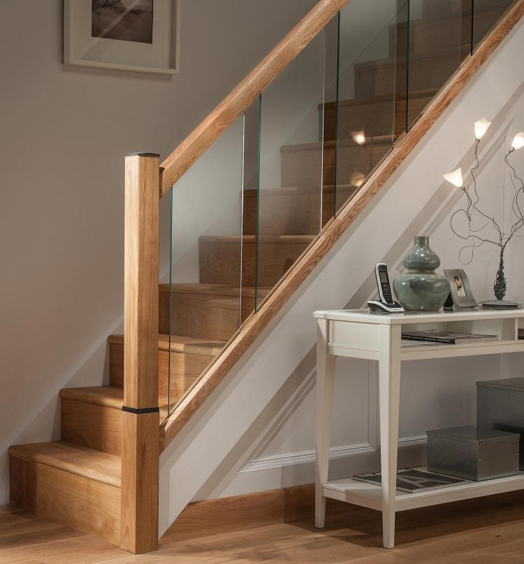 A picture of the Reflections Glass Balustrade range in a hallway including modern glass panels and oak handrails, base rails and newel posts.